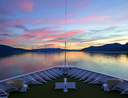 A sunset seen from the bow of a ship.