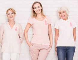 A row of smiling women wearing pink ribbons on their shirts
