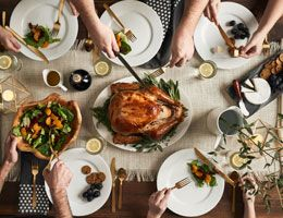 A birds-eye view of a roasted turkey and people gathered around a holiday table.