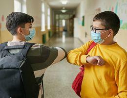 Two masked grade school kids touching elbows in a school hallway.