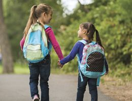 Two girls with backpacks holding hands as they walk down the street.