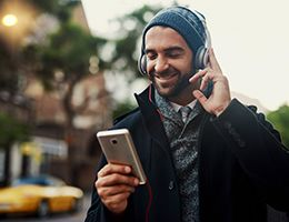 A man wearing headphones smiles at his smartphone.