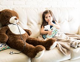 A young girl is sitting on a couch with a thermometer in her mouth and holding a box of tissues.
