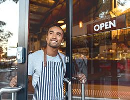 """A young man is opening the door to a restaurant. The door has a sign on it that says """"open."""""""