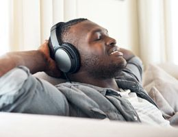 A relaxed man sitting on a couch with eyes closed and headphones on.