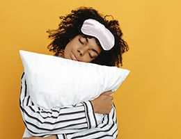 A woman wearing a sleep mask and hugging a pillow.