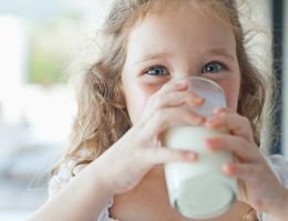 A child drinks a glass of milk.