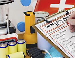 An emergency checklist on a clipboard with batteries, a radio, a flashlight and other supplies.