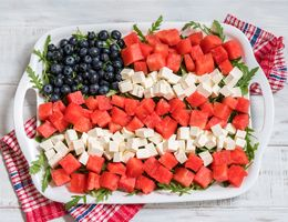 A platter of watermelon, cheese and blueberries arranged like an American flag.