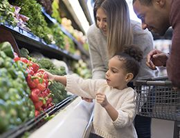 A young family shopping in the veggie section of a grocery store.