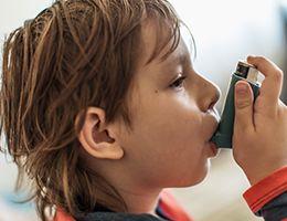 A young boy using an inhaler.