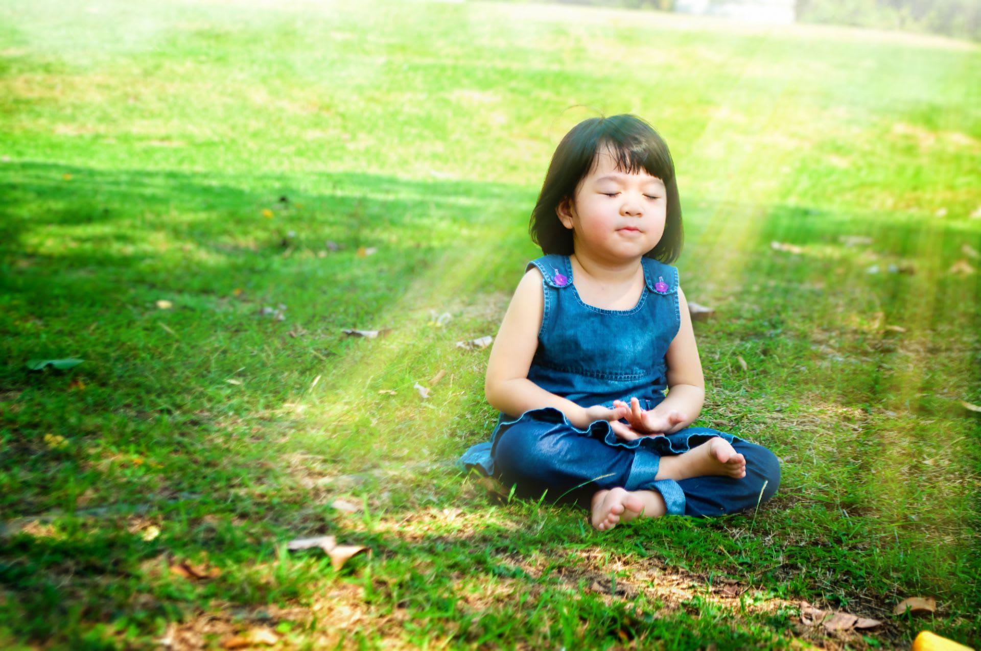 Mindfulness op school: meisje mediteert in het park