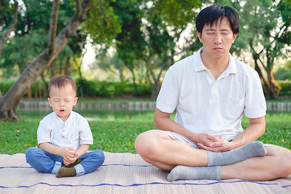kindermeditatie: vader en zoon met ADHD of ADD in meditatie