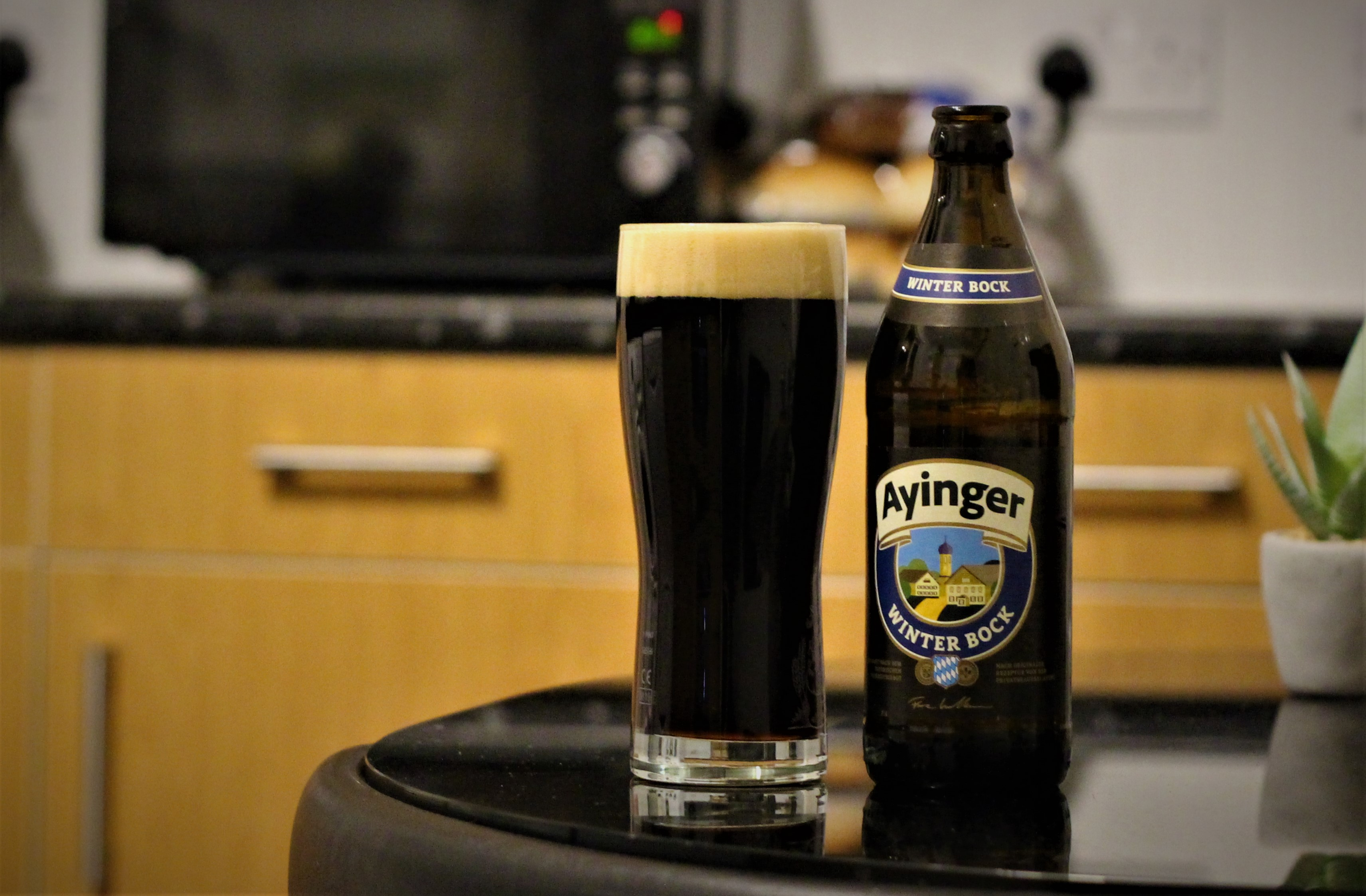 photo of ayinger beer in a glass next to the bottle