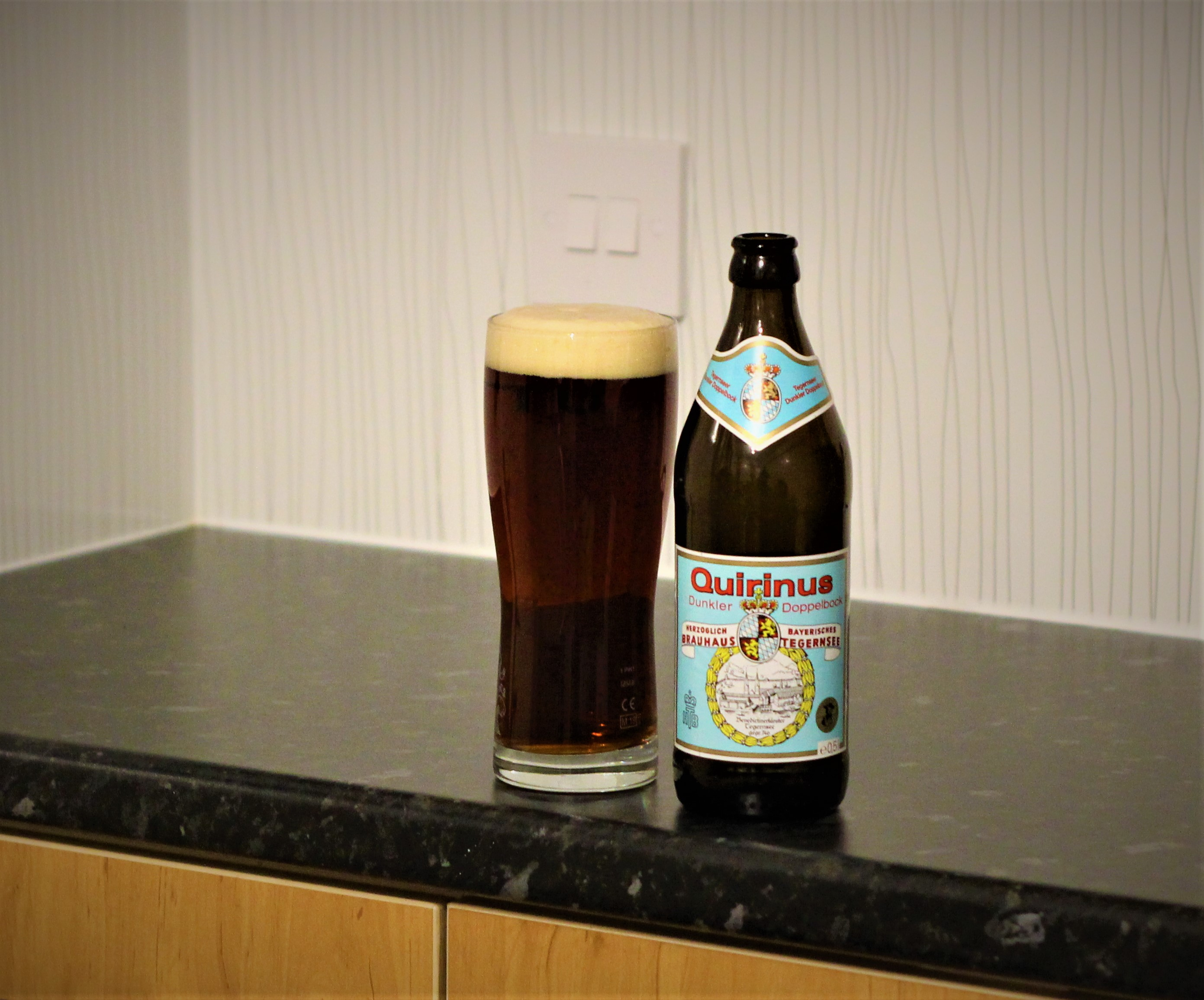 photo of tegernseer beer in glass next to bottle