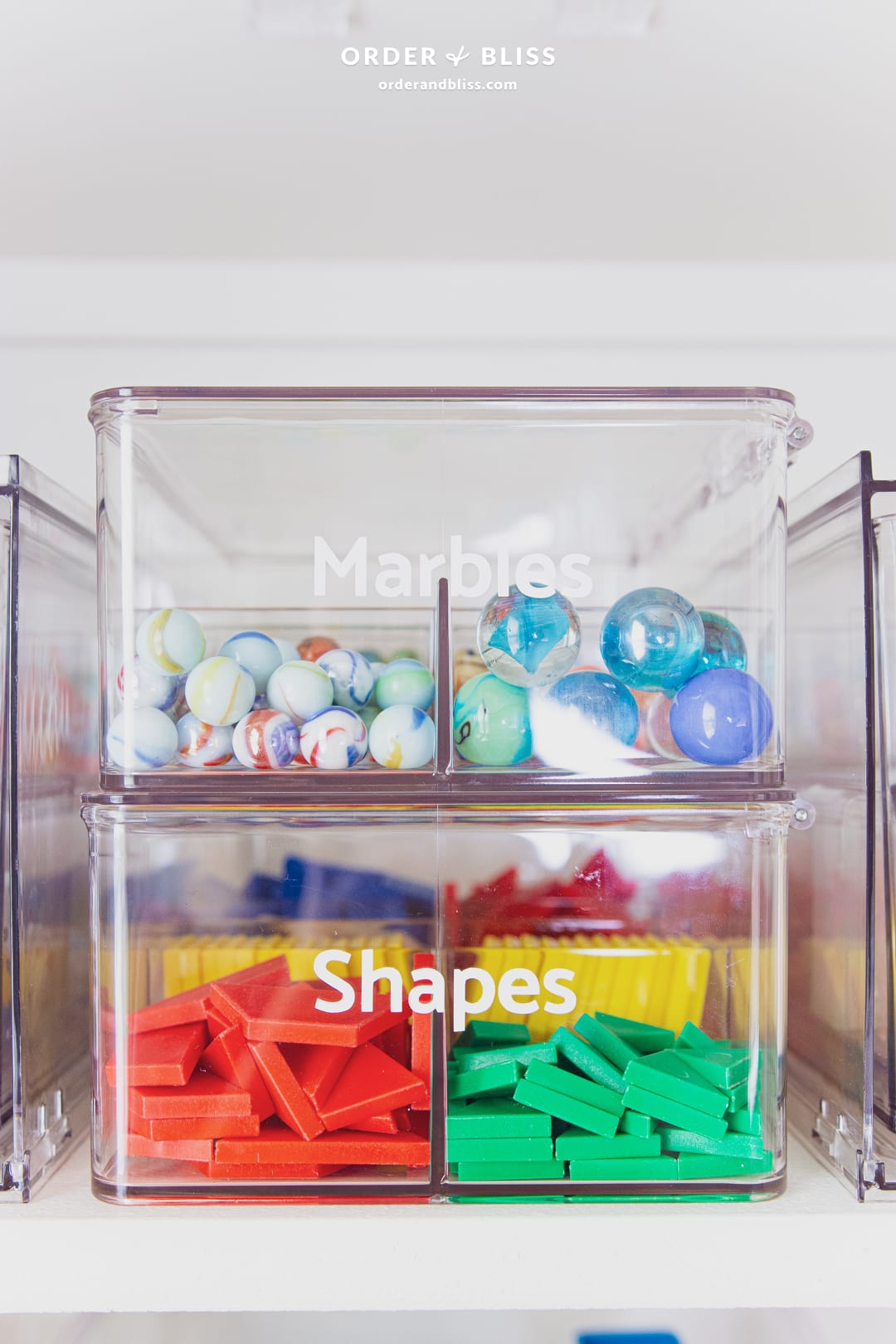 Clear stackable containers storing marbles and shapes