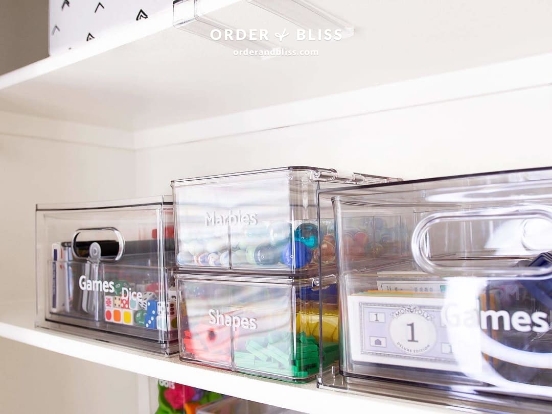 Clear organization bins with marbles, shapes, and games