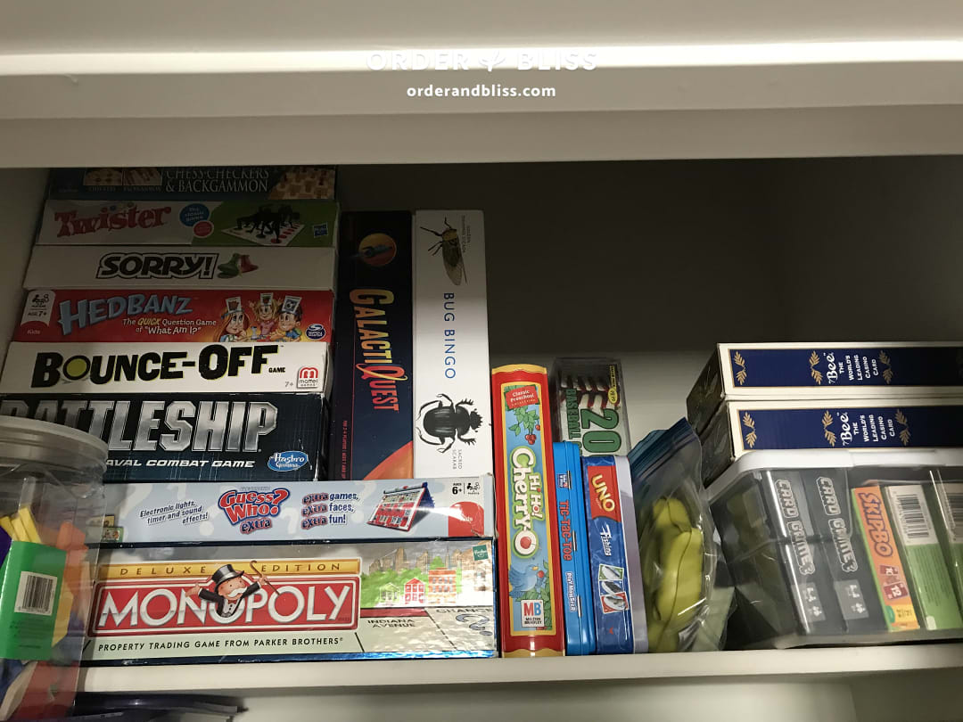 Before shelf of stacked board game boxes