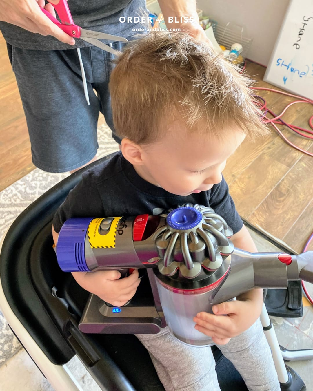 Toddler boy holding a vacuum during haricut