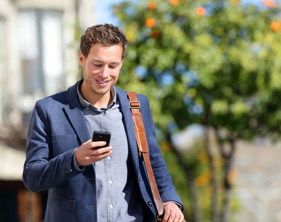 Image of a man typing on a mobile phone