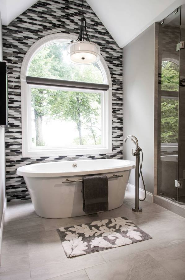 The accent wall enhances the tub as an focal point and visually divides the open bathroom floor-plan as part in a Bathroom Decor for 2020