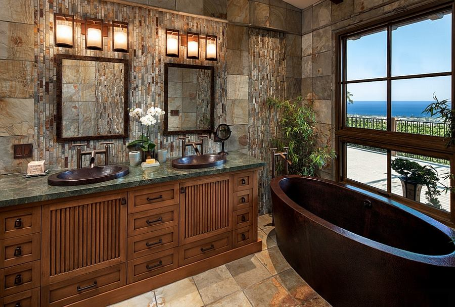 A huge wooden framed circular mirror is the centerpiece of this rustic yet modern bathroom. Black coned light fixtures highlight the mirror, while the simple vanity and sleek white marble countertop help balance the old and new.