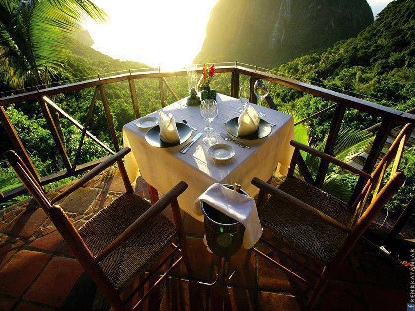 Dinner table & wicker chairs with view on the rain forest from the balcony