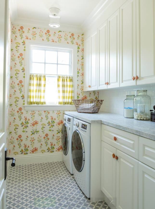 The floral design wallpaper brings this beautiful laundry room to life, With its cream color cabinetry And the white marble countertop is would fit mostly into any home design. And the window literally invited the sunlight in