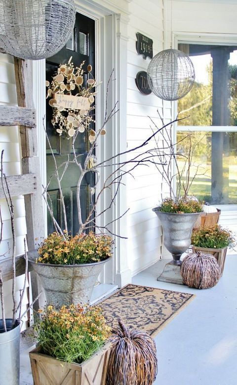 A crafty wreath made out of wood slices and twigs decorate a front door  now add a couple of pumpkins and you get a great fall entrance.