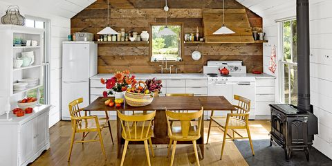 This rustic white kitchen loads autumnal appeal thanks to a bounty of recently chosen fall gifts  (apples, flowers, and squash) onto the screen
