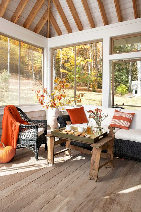 Wicker pieces, accented with burnt-orange accessories, offer to seat on this glassed-in porch
