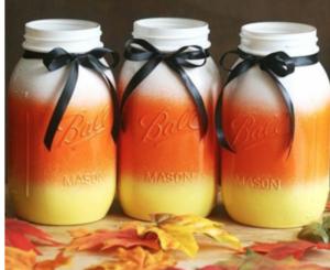 Candy Corn Mason Jars (source unknown) 3 Mason Jars + Orange, Yellow and White Spray Paint ($1 each at Walmart) + Black Ribbon (Dollar Tree)