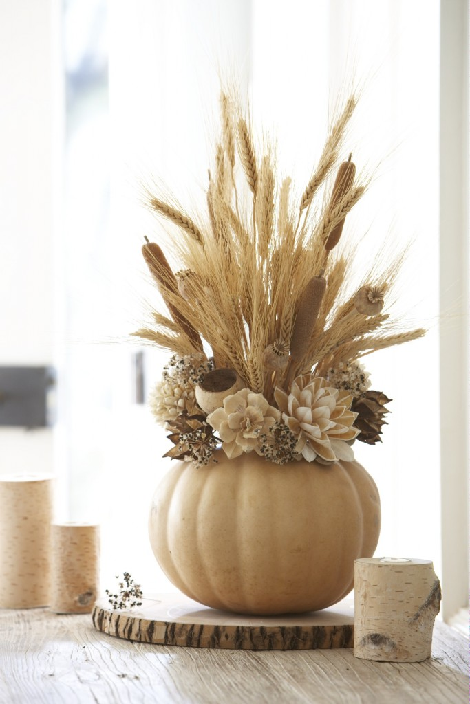 Dried foliage springs forth from a base of off-white flowers and a synthetic pumpkin. Wheat, dried cattails, and dried poppy blooms include height to the center of the display screen. Silk flowers call this center display screen, peaking out of the off-white pumpkin base. This round focal point works well on smaller sized table or sideboards.