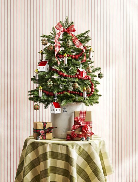 Grab a mini tree and set it into a tin bucket or like here in a stone ware crock. Use some left-over plaid ribbon. And decorate the tree with wooden beets, a plaid bow, and some ornaments. If it does not come pre lit clamp on a few battery operated candlesticks.