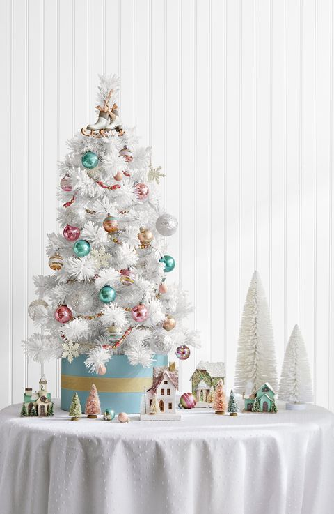 Here you find a solid white mini spruce setting the tone for a wintry landscape. Some pastel colored tree ornaments and a few decorative putz homes leading up to some cute ice-skate tree toper.   Shop for putz house kit