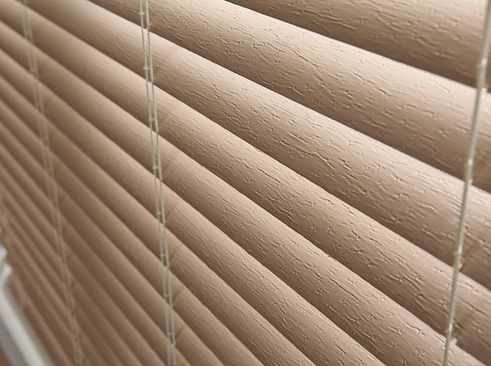 """Faux Wood Window Blinds are PVC Blinds that are made from a solid or foamed Poly Vinyl Chloride (PVC) plastic. PVC- blinds have really gained popularity over the past 20 years. They are usually 2"""" to 3 Inches wide. And the blind louvers surface is smooth. However, they are also available in a very luxurious and classy looking wood grain imitation."""