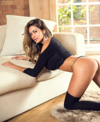 Leaning on a sofa in black lingerie