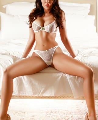 Sitting legs apart in white lingerie