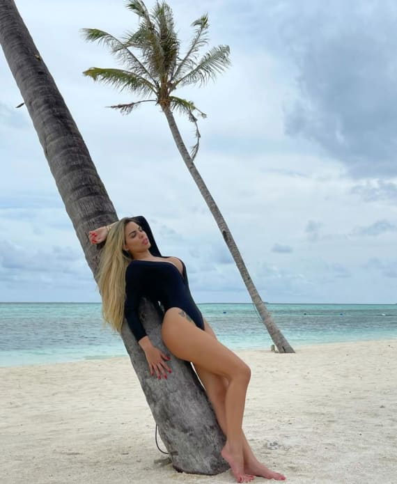 Sexy Latino Girl Standing against tree on the beach