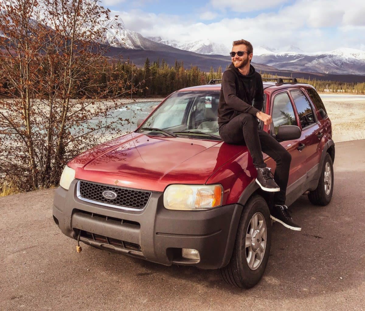 Kluk sedí na autě v kanadské přírodě