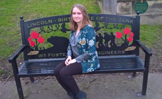 Studentka sedí v parku na lavičce