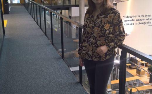 Studentka stojí ve školní chodbě a opírá se o zábradlí