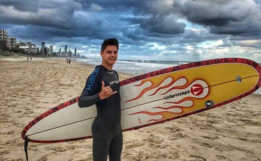 Mladík na pláži se surfem v ruce