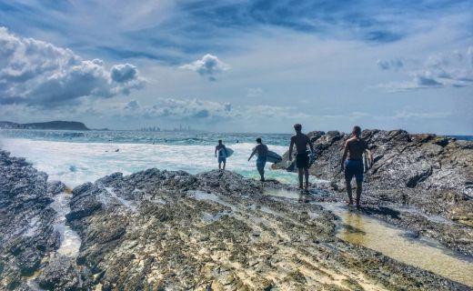 Serfaři kráčejí po pláži