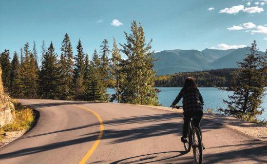 Dívka jede na kole kanadskou přírodou
