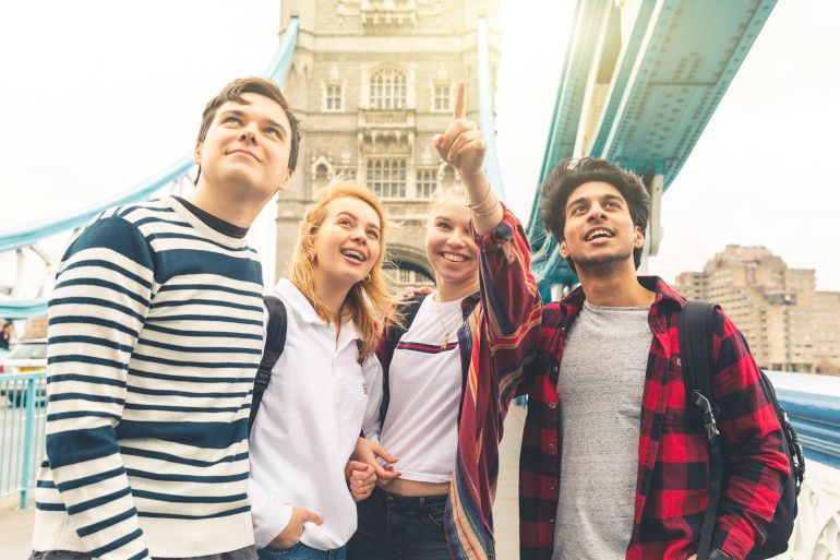 Happy students on Tower Bridge in London during school trip