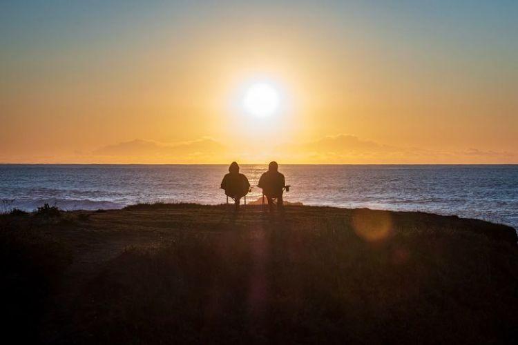 pessoas vendo por do sol em um penhasco