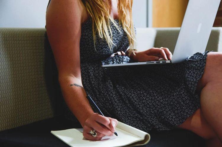 mulher mexendo no notebook e anotando