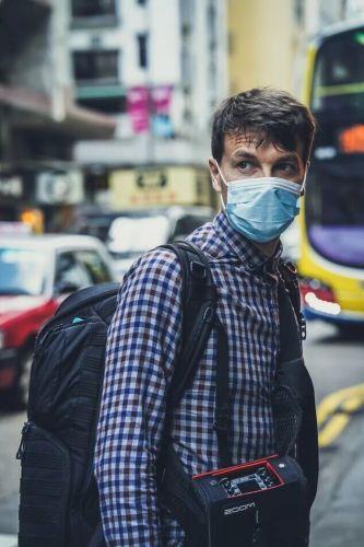 homem com máscara parado na rua