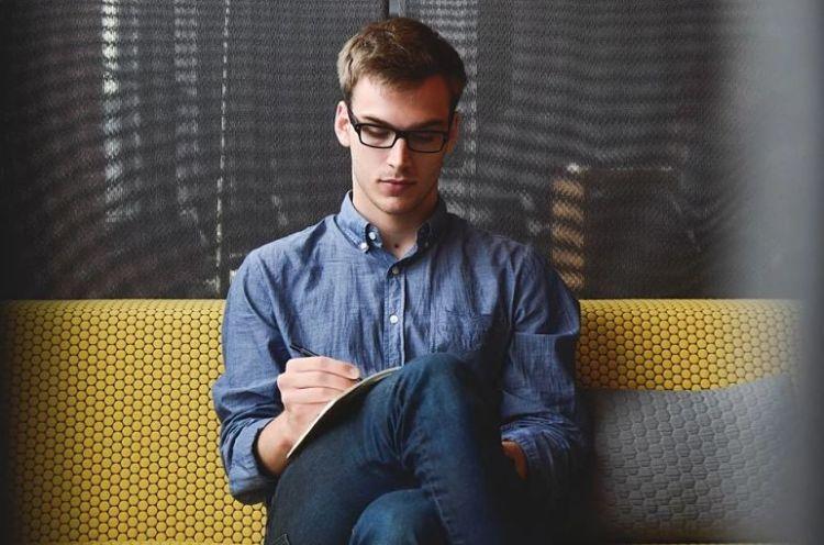 homem sentado de pernas cruzadas escrevendo